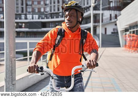 Male Courier Wearing Helmet Looking Away And Walking With Bicycle On The City Street