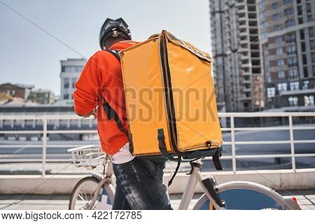 Man With Backpack With Food Looking Route At His Smartphone App While Riding To The Client