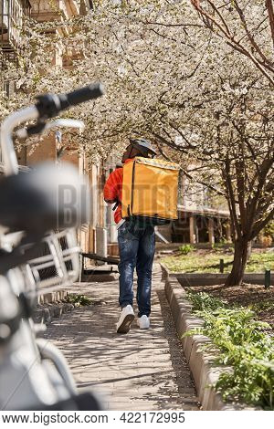 Courier With Yellow Backpack Looking For A Way To The Client While Delivering Orders