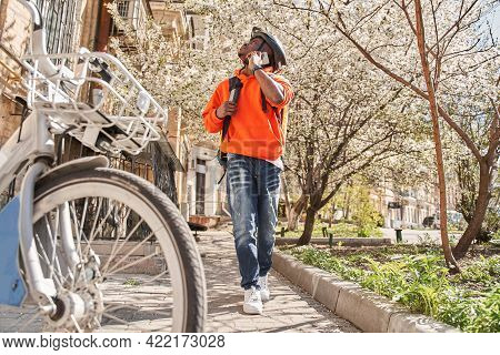 Food Delivery Courier Wearing Backpack And Helmet Chatting At The Smartphone