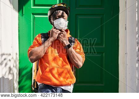 Man Wearing Helmet, Protective Mask And Delivery Backpack Standing Near Clients Door
