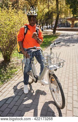 Guy Wearing Helmet Checking Order Via Mobile Phone