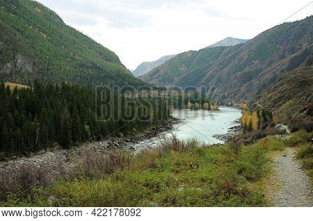 A Narrow Trail Running Along The Mountainside With A River Flowing Through The Autumn Coniferous For