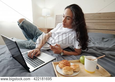 Serious Young Vietnamese Man With Wavy Hair Lying On Bed With Tray With Buns, Coffee And Apple And U