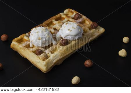 Fresh Belgian Waffles With Two Scoops Of White Ice Cream Poured With Chocolate And Hazelnuts On A Bl