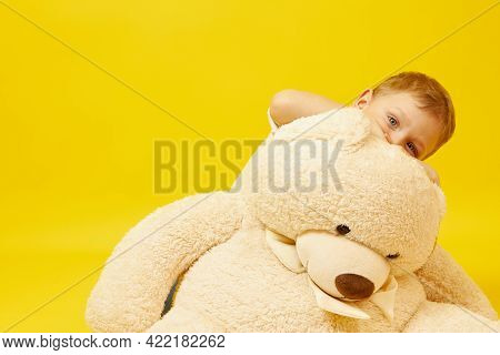 A Sad Blue-eyed Boy With A Teddy Bear On A Yellow Background. The Emotion Of Sadness, Melancholy, Lo