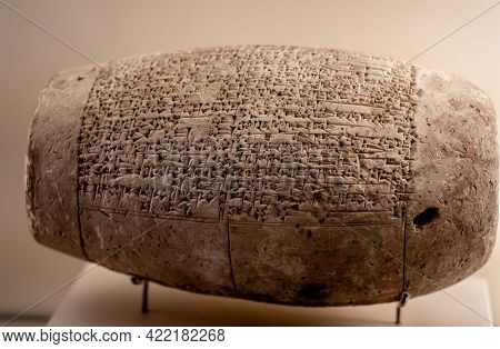 Berlin, Germany - 18 September 2019: Clay cylinder from Babylon in Vorderasiatisches Berlin museum. Antique religion stone cult with carved pictogram and script. Art object in Germany collection