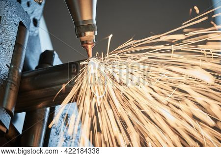 CNC laser cutting of round metal rolling pipes on tube laser cutting machine with sparks