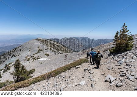 San Gabriel Mountains National Monument, California, USA - May 23, 2021:  Hikers on the popular Devils Backbone trail near the summit of Mt Baldy.