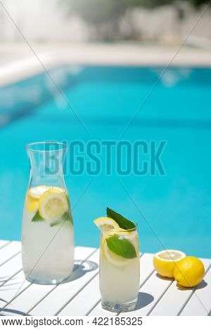 Homemade Lemonade In Glasses With Lemon Slice, On White Table, In The Edge Of The Pool With Turquois