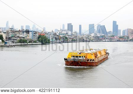 Cargo Ship On The River With View Of The City.