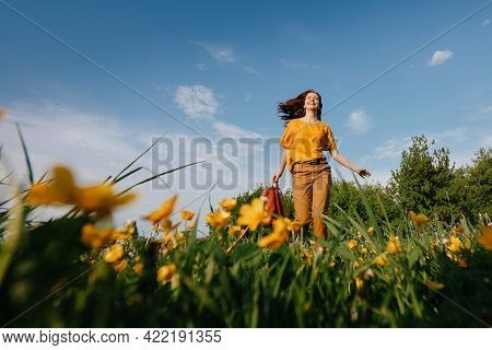 A Happy Young, Slender Girl Runs Across The Field, Bottom View, Inhaling The Aroma Of Fingers Of Yel