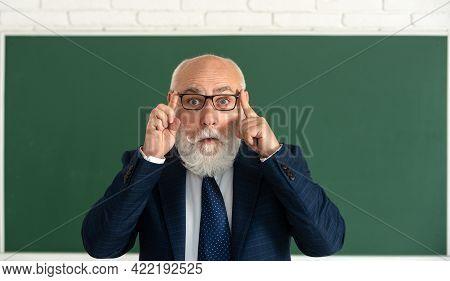 Funny Senior Professor In Glasses. Surprised Grey Hair Professor Near Blackboard. Think.