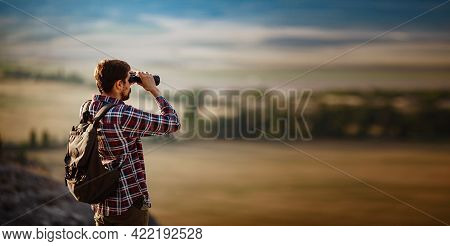 Guy Looking At Binoculars In Hill. Man In T-shirt With Backpack.