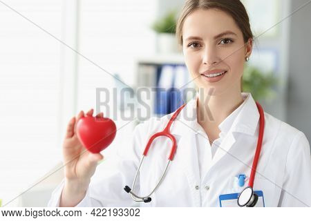 Portrait Of Female Doctor Cardiologist With Small Heart In Her Hand