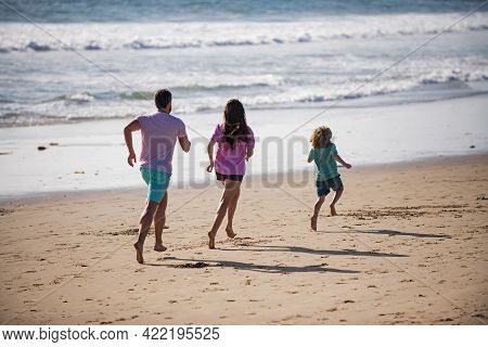 Happy Young Family Run And Jump On Summer Beach. Child With Parents Running And Jumping. Concept Of