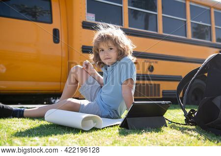 Pupil Does School Homework Laying On Grass In The Park Near School Bus. School Kid Outdoor.