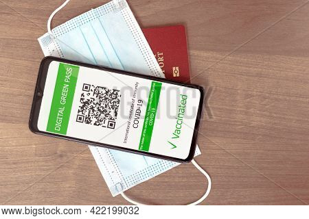 Digital Green Pass Concept: Smartphone Over A Passport And A Surgical Mask On A Table