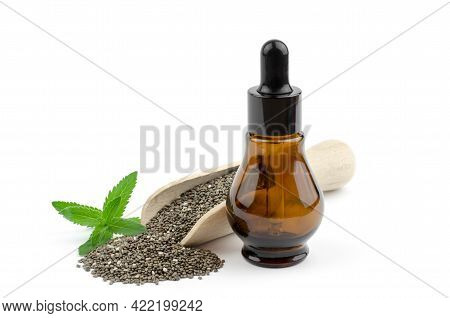 Chia Seeds In A Wooden Scoop With Green Chia Leaves And Seed Oil On A White Background. Chia Seed Oi
