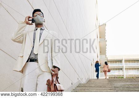 Handsome Young Businessman In White Suit And Medical Mask Walking Down The Stairs Leaving Office Bui