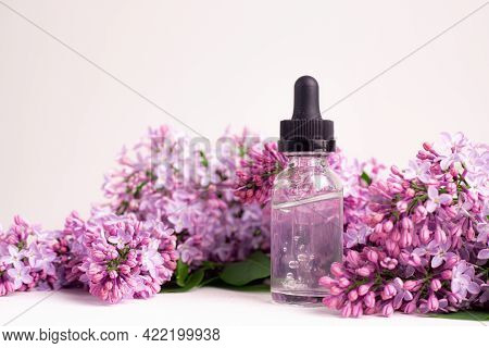 Hyaluronic Acid Bottle And Lilac On A White Background . Beauty Container. Skin Care. Vitamins For T