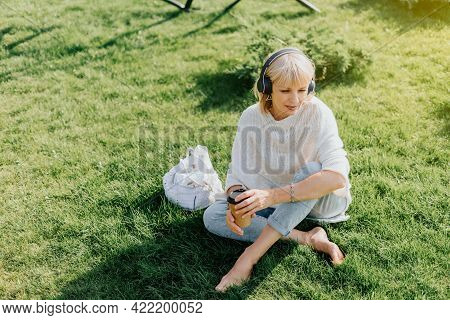 Adult Woman In Headphones Sitting On Green Grass Outside In Summer Park At Sunset. Happy And Smiling