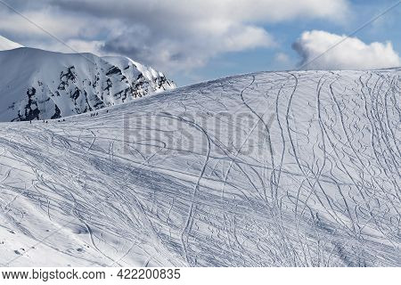 Snow Off Piste Slope For Freeriding With Traces From Skis, Snowboards And Silhouette Of Freeriders A