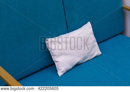 Blank White Pillow On A Blue Sofa. Close-up Of Pillow On A Couch.