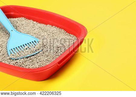 Cat Litter Tray With Filler And Scoop On Yellow Background, Closeup. Space For Text