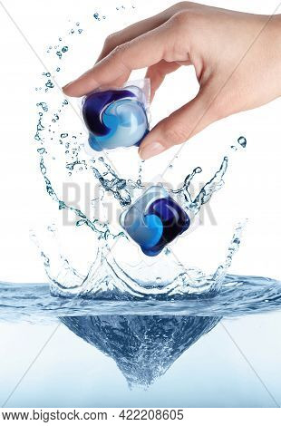 Woman Throwing Laundry Capsules Into Water On White Background, Closeup. Detergent Pods