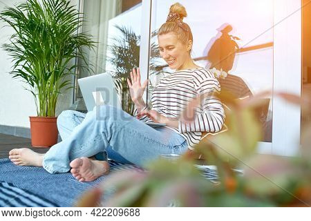 Working from home. Woman talking on video call with Family, using laptop. Online chat. Spend free time on terrace. Staying connected, Social distancing, internet, chatting.