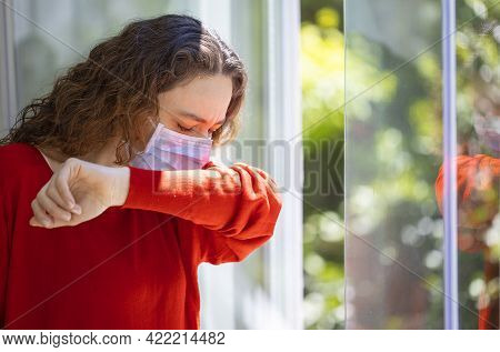Young Woman With Face Mask Sneezing Into Elbow