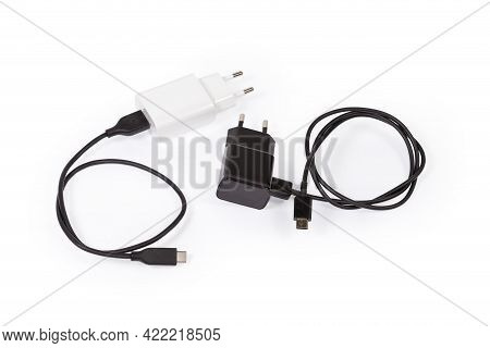 Two Different Ac Adaptors With Ac Europlugs And Connected Appropriate Usb Cables For Batteries Charg