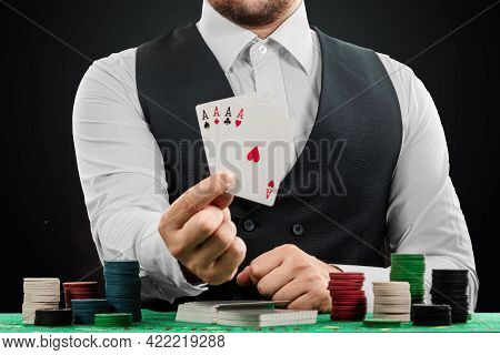 Male Dealer At The Casino At The Table. Casino Concept, Gambling, Poker, Chips On The Green Casino T