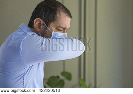 Young Man With Face Mask Sneezing Into Elbow