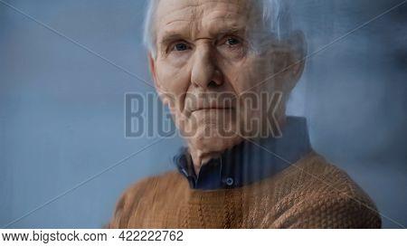 Portrait Of Elderly Man Looking At Camera Through Rainy Window On Grey Background Behind Rainy Glass