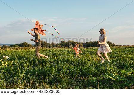 Happy Family Flying A Kite In Field.