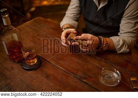 Man with guillotine cuts a cigar, tobacco smoking