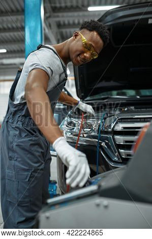 Male worker refills air conditioner, car service