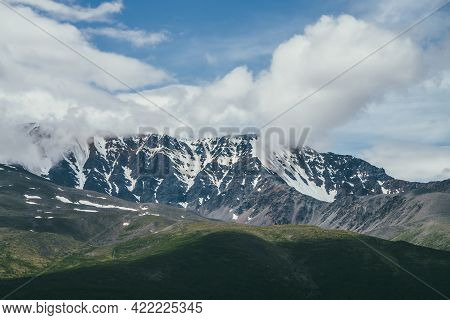 Awesome Mountains Landscape With Big Snowy Mountain Ridge Among Low Clouds In Blue Sky. Atmospheric
