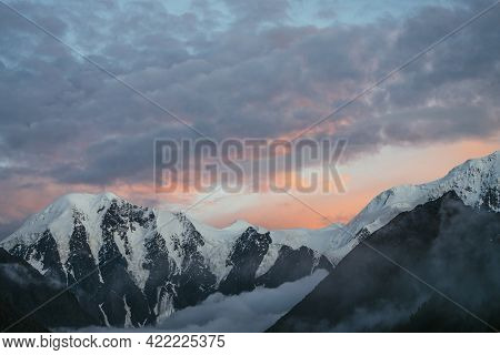 Atmospheric Mountain Landscape With Great Snowy Mountains And Low Clouds In Valley Under Violet Oran
