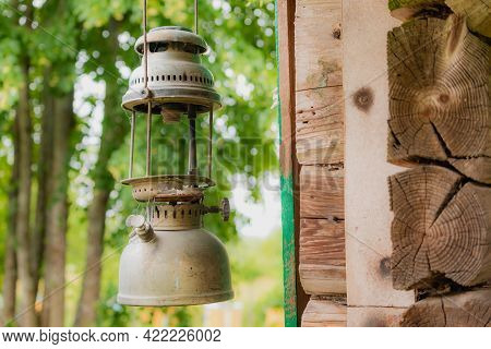 Old, Broken And Rusty Oil Lamps Hanging Near The Old Wooden Wall. Lithuanian Village At Summer Seaso