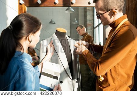 Two young fashion designers working over new jacket on dummy
