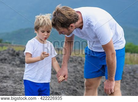 Father Son Or Adult Younger Brother Walk Together. Boy Found Show Holds Unusual Stone In Hand Finger