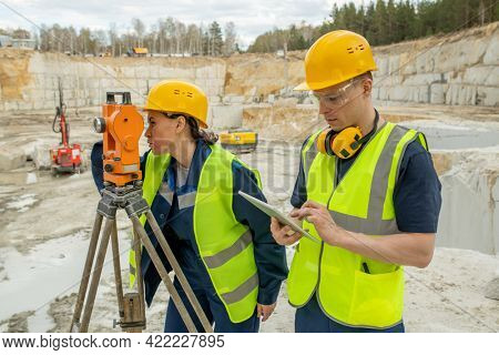 Female engineer using geodetic station while her colleague scrolling in tablet