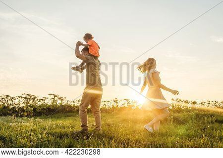 Happy Family Playing On Sky Sunset Background.