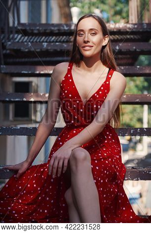 Street Fashion: Lovely Sweet Girl In Red Dress On Staircase. Portrait Of Pretty Smiling Young Woman