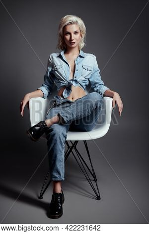 Studio Fashion: Beautiful Smiling Young Woman In Blue Shirt And Jeans. Cool Informal (rock) Girl Sit