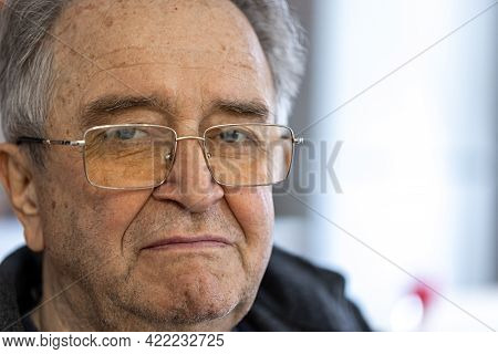 Close Up Portrait Of An Old Man With A Sad Look.
