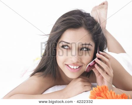 Asian Woman In Bed Talking On Her Cell Phone